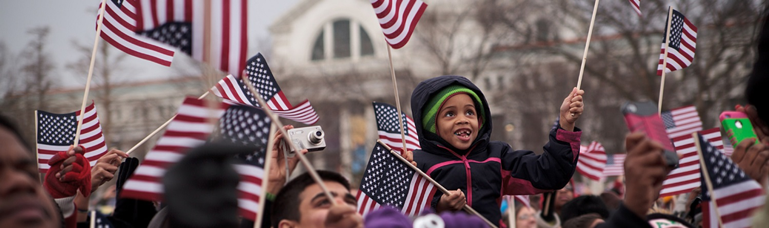 Arina Sangfield, 7, sits atop her fathers shoulders excitingly waving the American flag on the National Mall as President Barack ObamaÕs face appears on a large screen during his Inauguration, Monday, January 23, 2013.